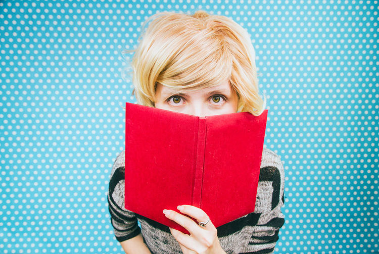 Portrait Of Woman Holding Red Book Against Blue Polka Dots Wall