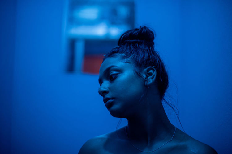 Portrait of young lady in room with blue light