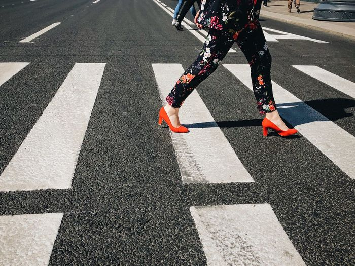 Low Section Of Woman Crossing Road In City