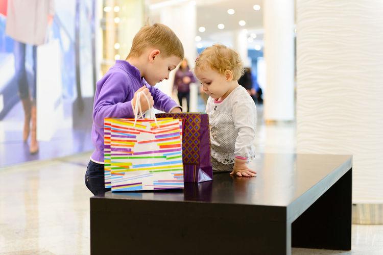 Cute sibling looking at bag while sitting at shopping mall