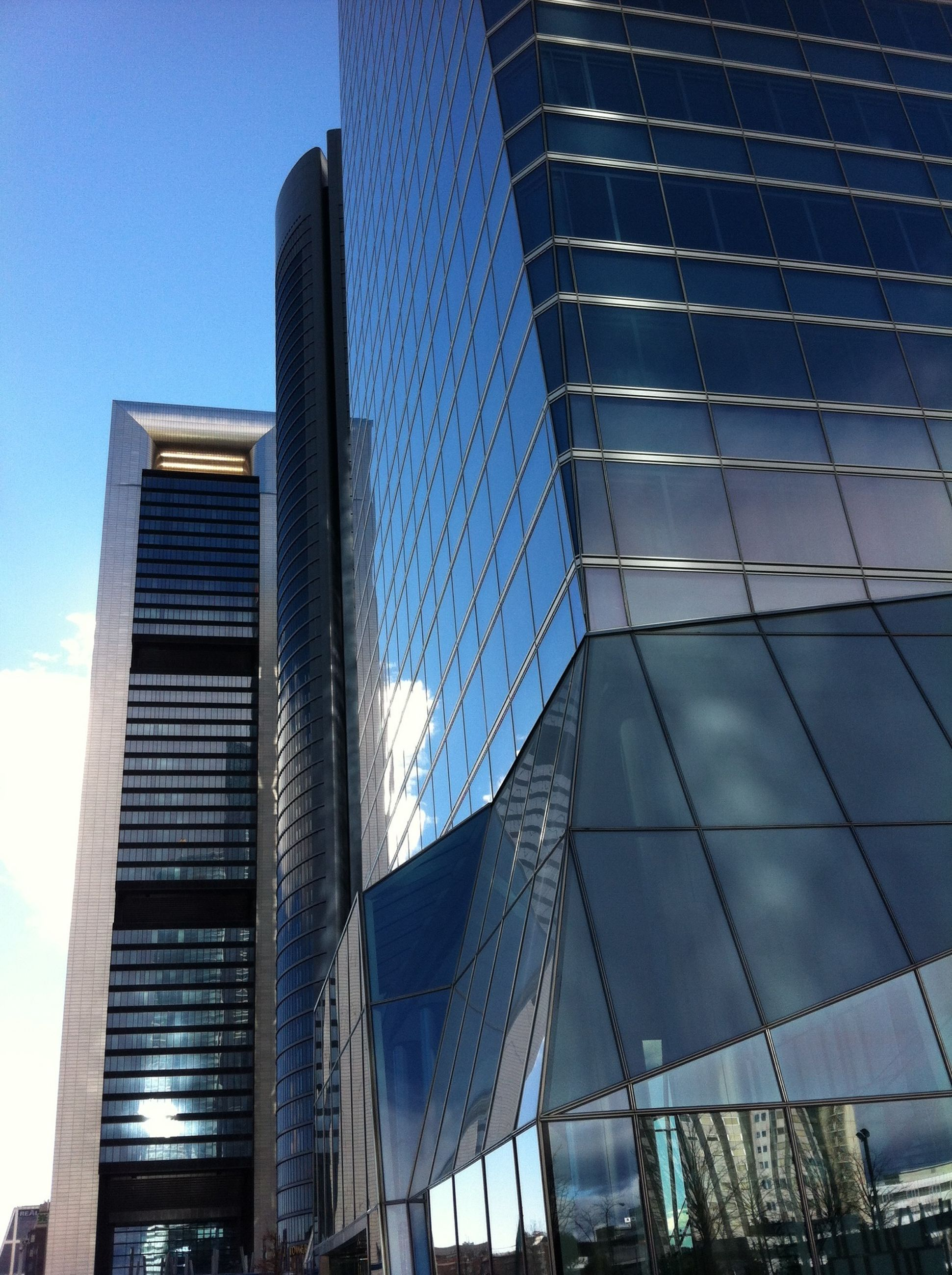 architecture, built structure, building exterior, low angle view, modern, city, office building, skyscraper, building, glass - material, blue, tall - high, sky, reflection, tower, city life, day, outdoors, clear sky, capital cities