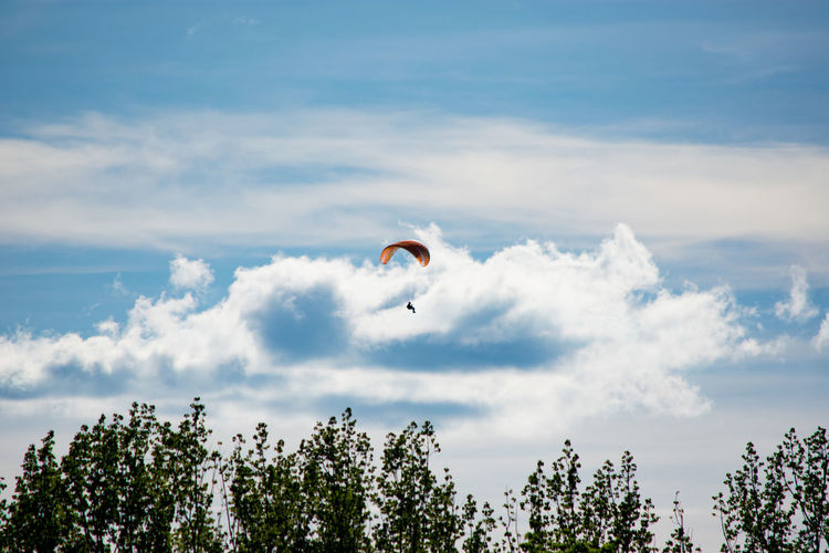 Mid Distance View Of Person Paragliding Against Cloudy Sky