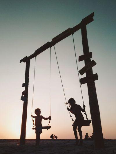 Children swinging on field against sky during sunset