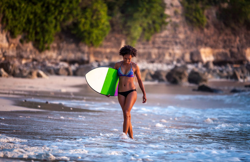 Surfer girl with afro hairstyle walking with surfboard on Padang Padang beach at sunset in Bali, Indonesia Afro The Traveler - 2018 EyeEm Awards Beach Hairstyle Leisure Activity Lifestyles Motion Outdoors Real People Sea Surfboard Surfer Girl Surfing Trip Walking Women Summer Sports