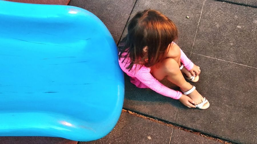 High angle view of sad girl sitting by slide at playground