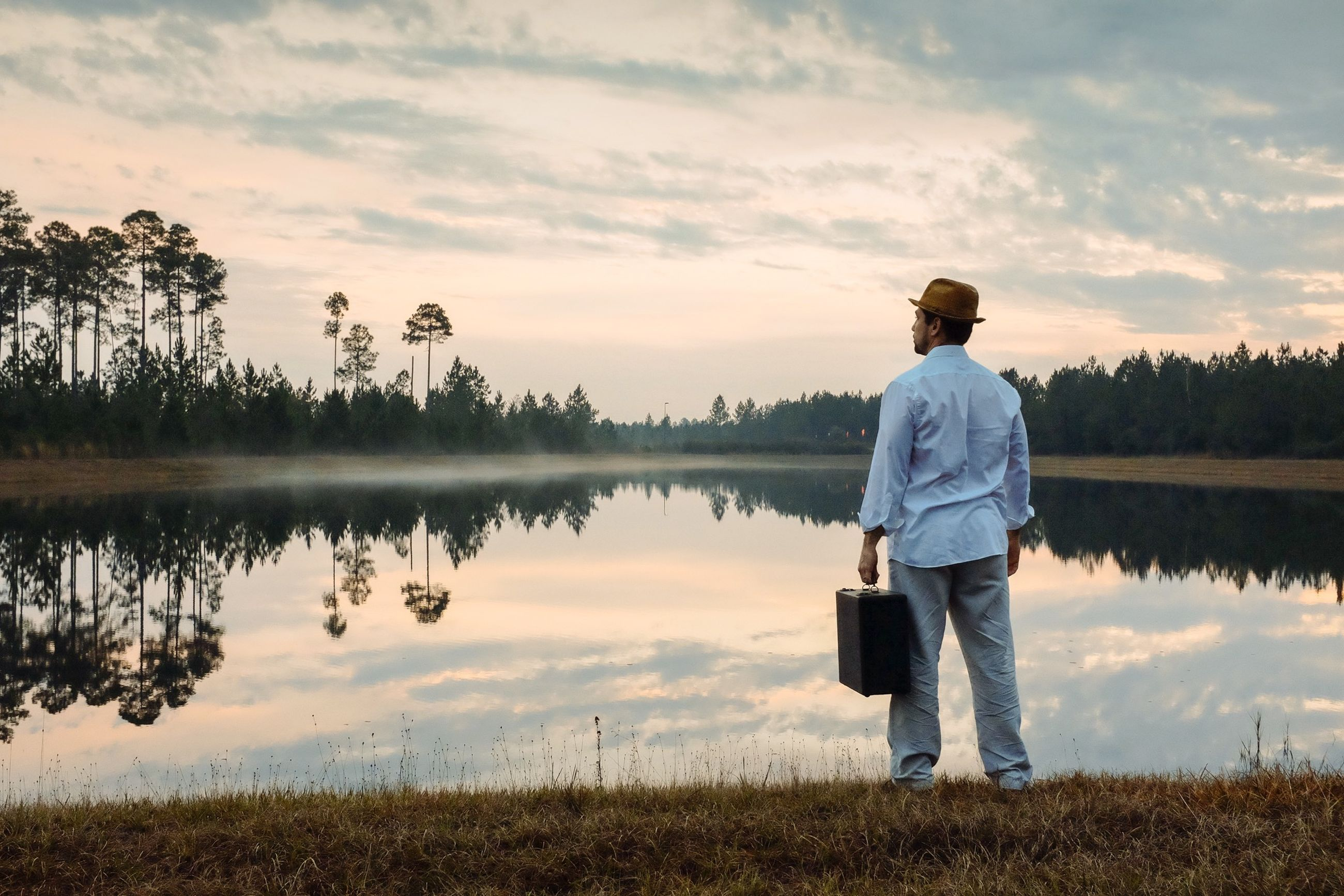 water, sky, lake, reflection, tranquility, lifestyles, leisure activity, standing, tranquil scene, rear view, scenics, beauty in nature, nature, grass, cloud - sky, full length, casual clothing, men