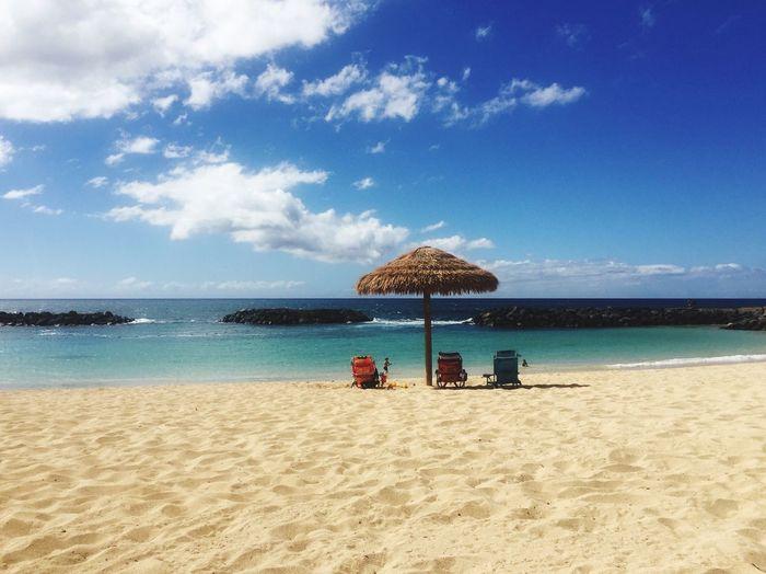 Sun Loungers On Beach Against Blue Sky