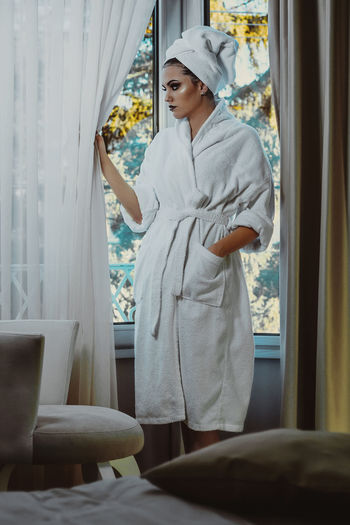 Beautiful glamorous woman in bathrobe One Person Real People Standing Indoors  Three Quarter Length Window Young Adult Lifestyles Women Leisure Activity Adult Young Women Curtain Casual Clothing Day Bathrobe Looking Beautiful Woman Contemplation Relaxing Pure Hotel Room Traveling Lady Fresh