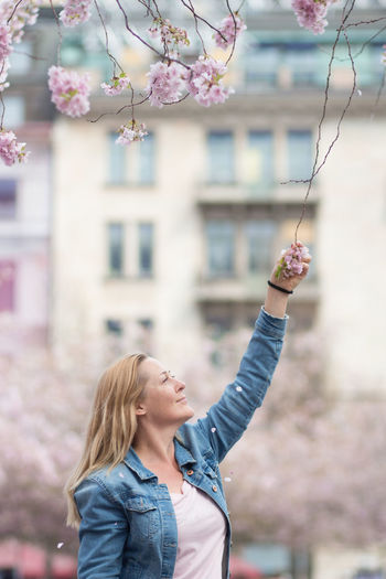 Smiling woman holding flower on tree