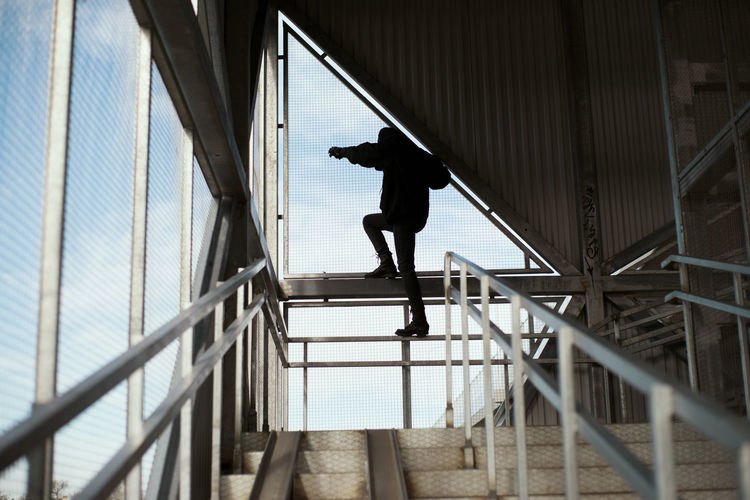 Low angle view of silhouette man standing on railing