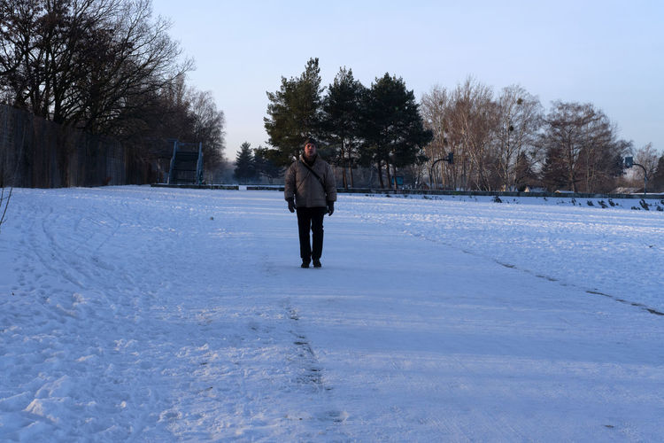 Man on snow covered field against sky