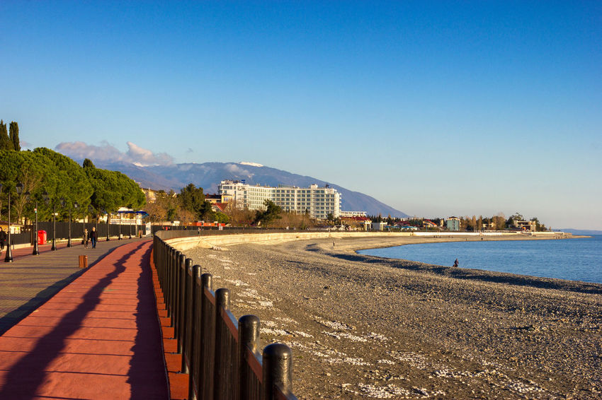 Beauty In Nature Blue Built Structure Clear Sky Coastline Day Diminishing Perspective Long Mountain Nature No People Outdoors Scenics Shore Sky Sunny The Way Forward Tourism Tranquil Scene Tranquility Travel Destinations Walkway Water