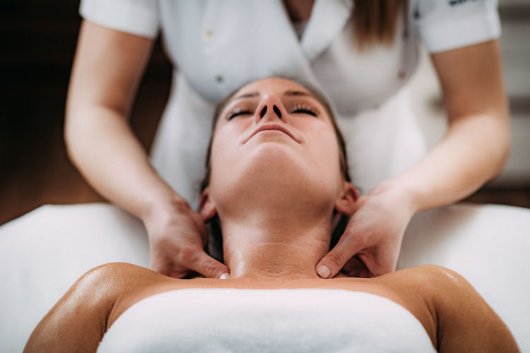 Midsection of massage therapist massaging female customer in spa