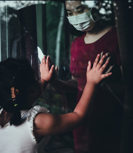 Mother wear face mask meeting daughter and touching hand through the window