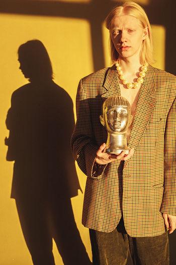 Portrait of man holding bust