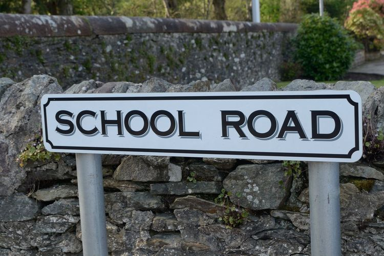 School Road sign Communication Text No People Day Sign Western Script Nature Close-up Information Solid Outdoors Information Sign Focus On Foreground Capital Letter Wall Rock Rock - Object Plant Non-western Script Script Stone Wall Message School Road