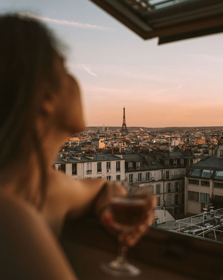 Close-up of woman holding wineglass looking at city