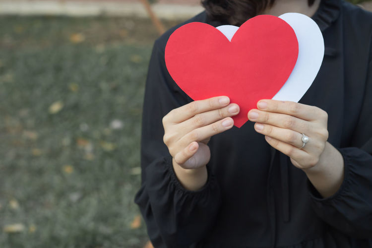 Close-Up Of Woman Holding Heart Shape Paper