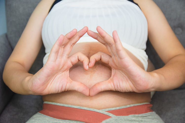 Midsection of woman with heart shape sitting on floor
