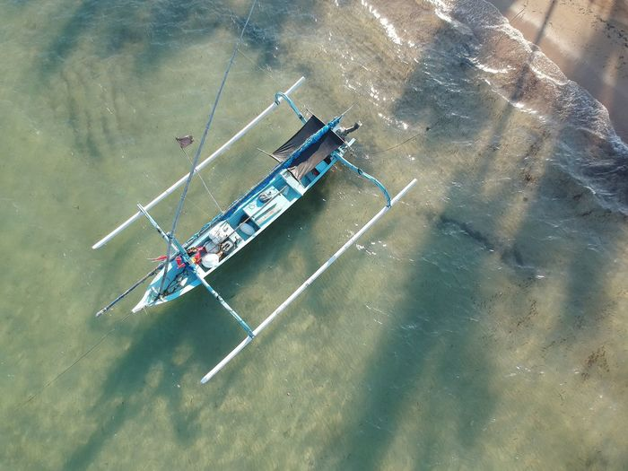 Traditional Indonesian boat moored at Sanur beach, Bali. Colorful Wooden Boat Sand & Sea South East Asia Idyllic Beach Paradise Bali Sanur INDONESIA Traditional Boat Vacations Water Transportation Nautical Vessel Summer Beach Life Water Nautical Vessel Teamwork Group Of People Aerial View High Angle View Crew Sky Outrigger Moored Longtail Boat Motorboat Mast Boat Going Remote