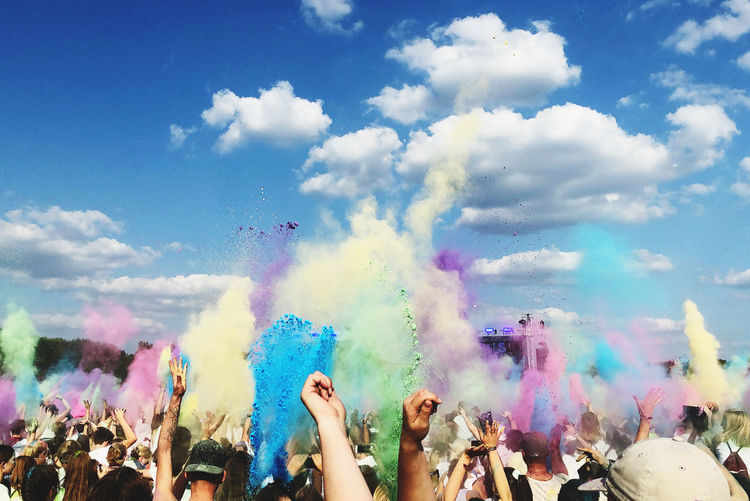 People throwing colored powder in air during holi festival against sky