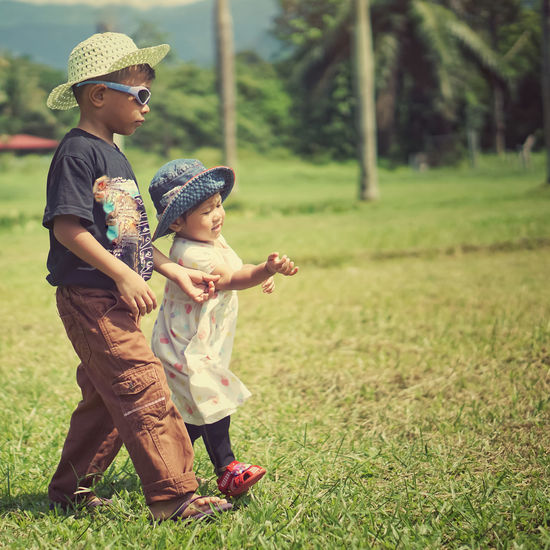 Child Childhood Full Length Smiling Togetherness Tree Boys Happiness Agriculture Rural Scene Sun Hat Blooming Straw Hat Babyhood Growing Family Bonds Farmland Cowboy