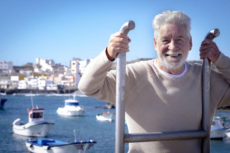 Portrait of man holding boat against sky