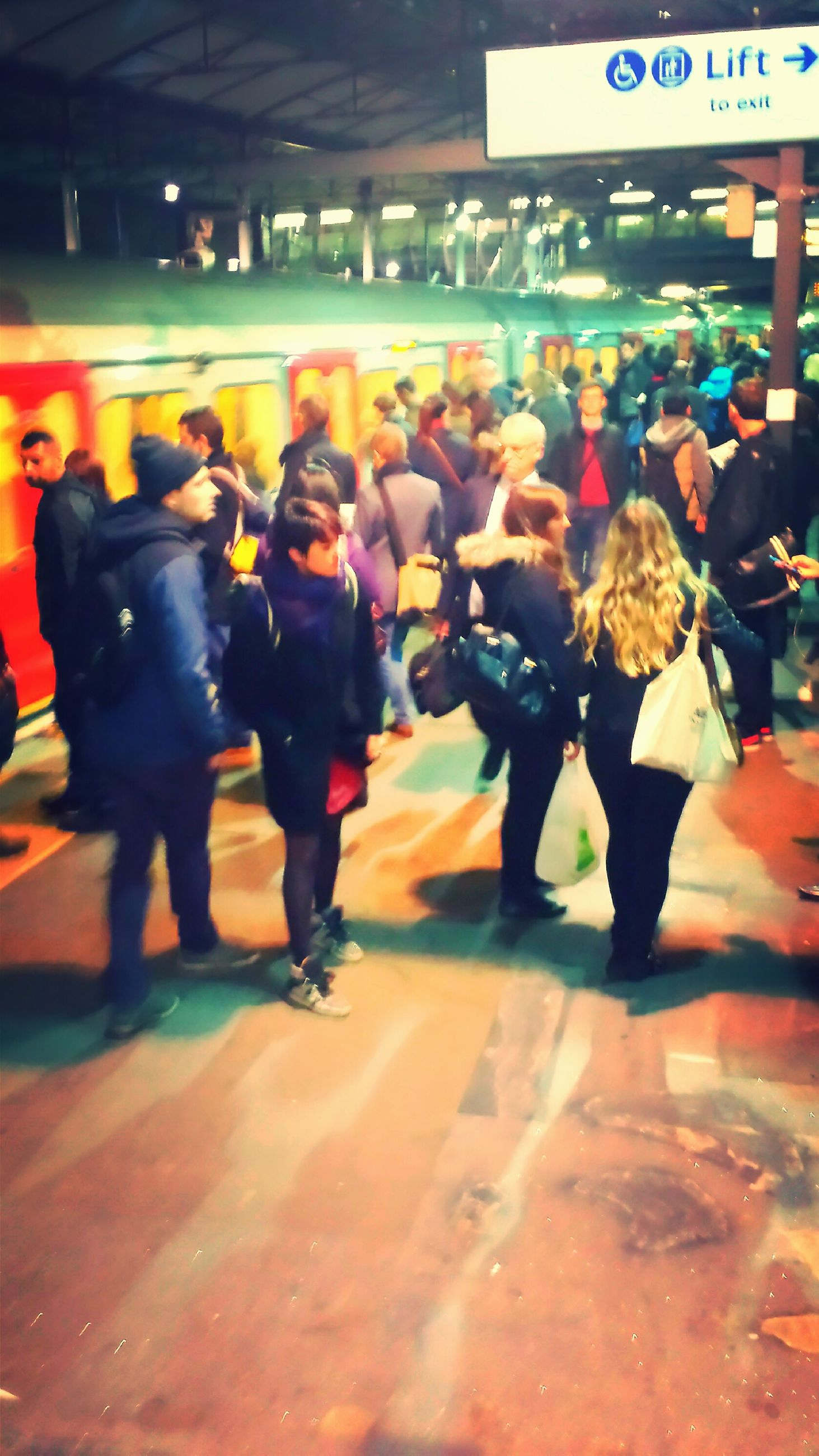 men, lifestyles, person, illuminated, night, leisure activity, large group of people, street, walking, full length, city life, standing, casual clothing, incidental people, city, text, group of people, store, blurred motion
