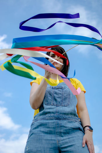 Low section of woman standing against the sky waving with rainbow ribbons.