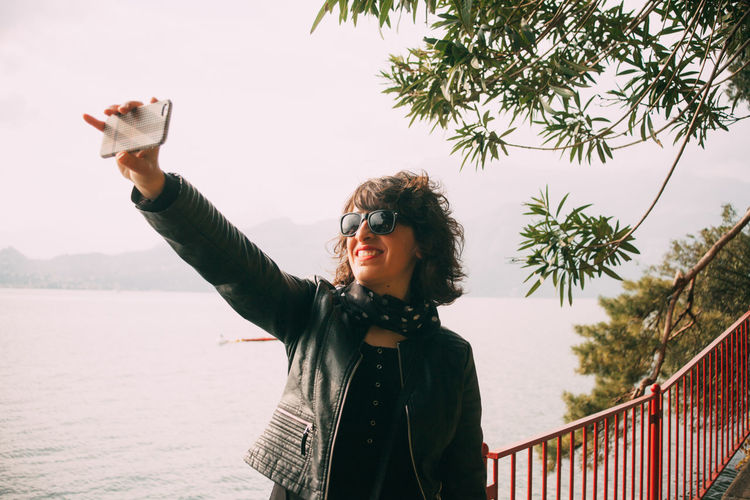 Smiling woman taking selfie with smart phone while standing by lake at park