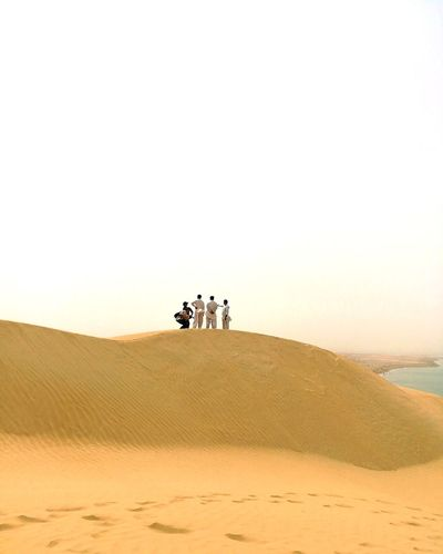 People standing on sand dune in desert against clear sky