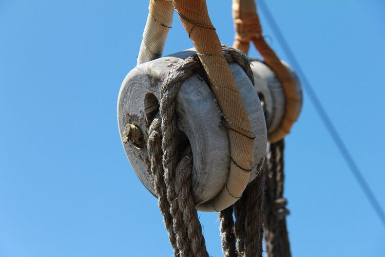 Close-up of ropes on wooden pulley against clear blue sky