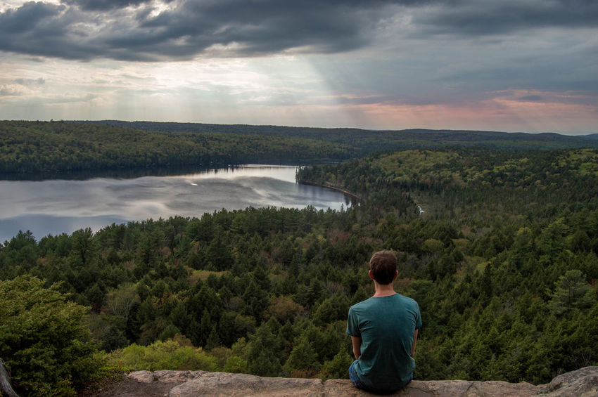 Young adult sitting on rock looking out over river en forest Beauty In Nature Cloud - Sky Forest Lake Lake View Looking At View One Person Outdoors Rear View Scenics Young Adult Adventure Algonquin Park Algonquinprovincialpark Algonquin Provincial Park Canada Breathing Space Investing In Quality Of Life Been There. Done That. Lost In The Landscape