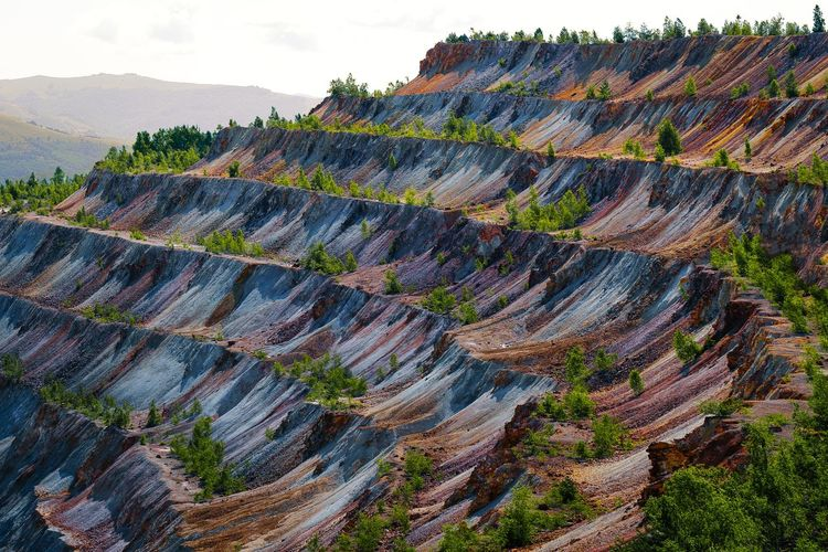 Scenic view of open pit mine. rock formations against sky