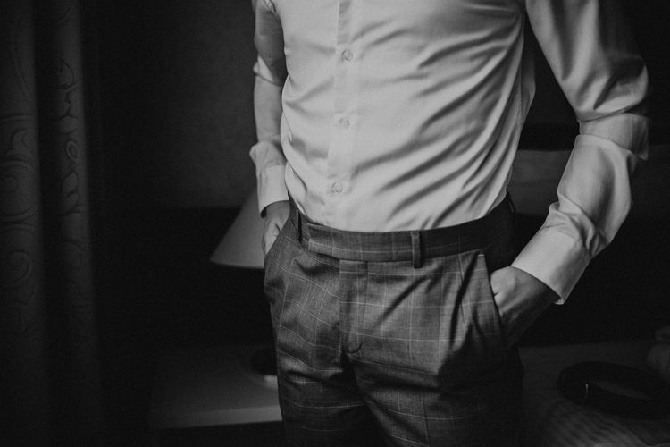 Midsection of man standing with hands in pockets