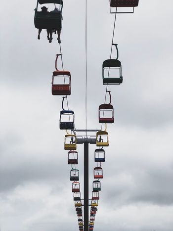 Chair lift at the fair grounds Chair Lift Sky Cloud - Sky Low Angle View Day Nature No People Ski Lift Lighting Equipment Overhead Cable Car Cable Car Communication Cable Hanging Outdoors Transportation Technology Connection Snow Sign Light