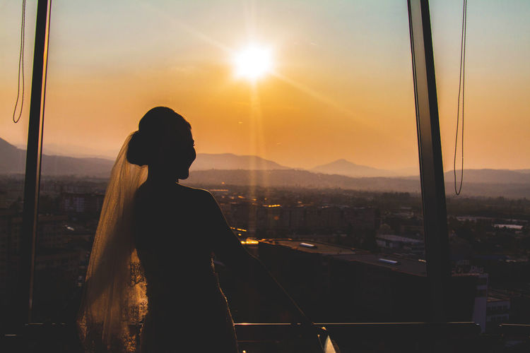 Silhouette woman standing on city against sky during sunset