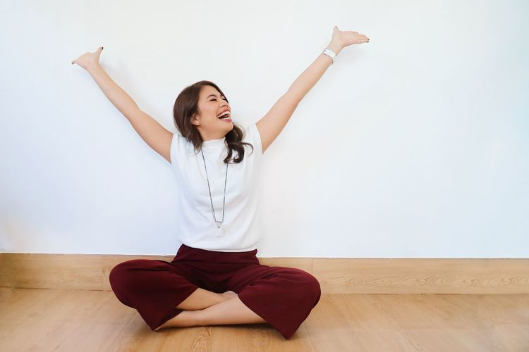 Full length of young woman against white wall