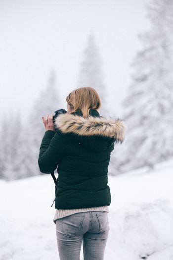 Rear view of woman standing on snow covered landscape