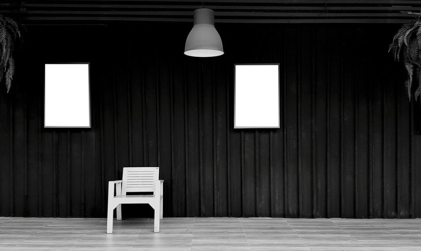 Empty chairs and table in illuminated room