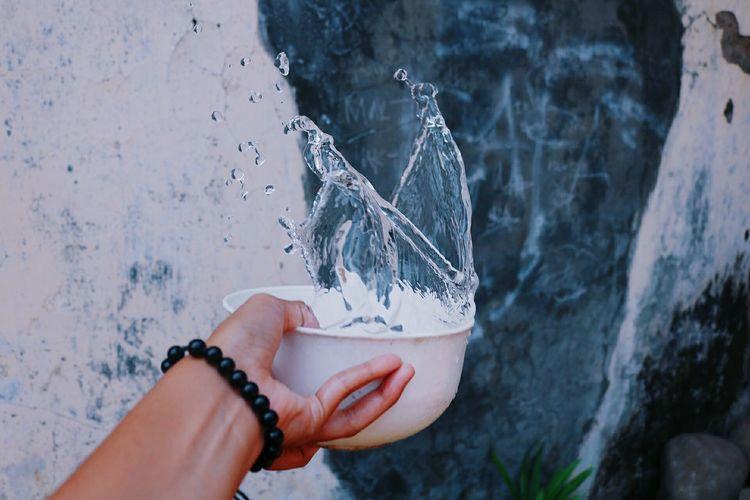 Hand splashing water in bowl