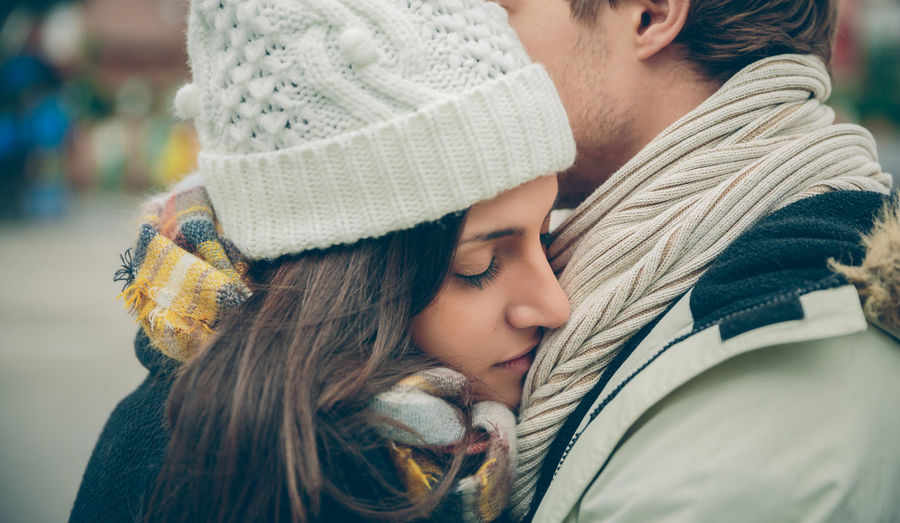 Closeup of young beautiful couple with hat and scarf embracing in a cold autumn day. Love and couple relationships concept. Woman Cold Winter Hat Scarf Horizontal Rain Girl Young Female Outdoors Autumn Fall Real People Caucasian Two People Couple Love Realtionship Man Male Umbrella Happy Embracing Hugging