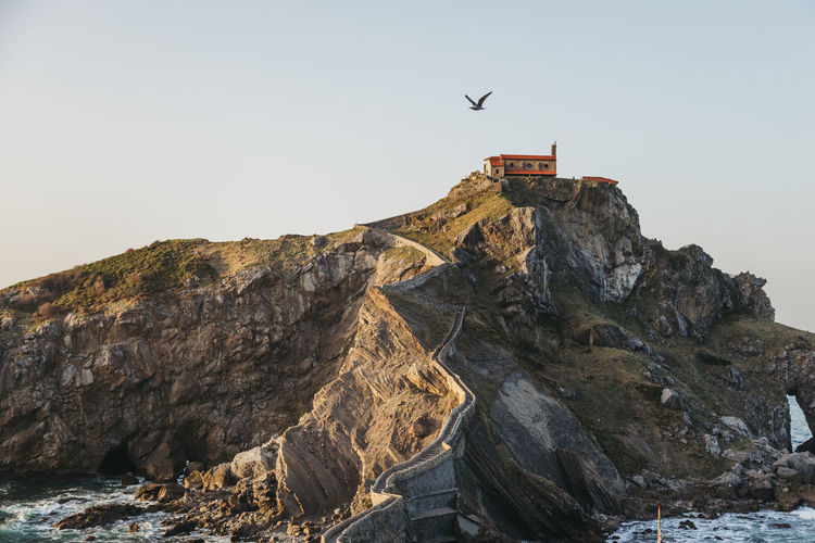 Low angle view of birds flying over rocks