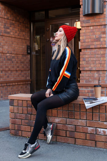 Full length of woman sitting on bench against brick wall outdoors