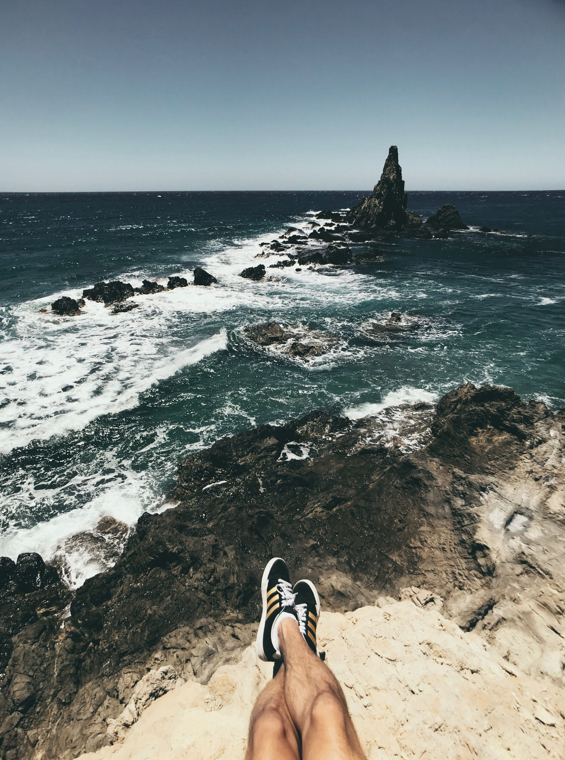 sea, water, beach, land, horizon, sky, personal perspective, horizon over water, low section, human body part, scenics - nature, nature, human leg, one person, beauty in nature, body part, clear sky, rock, day, outdoors, human foot
