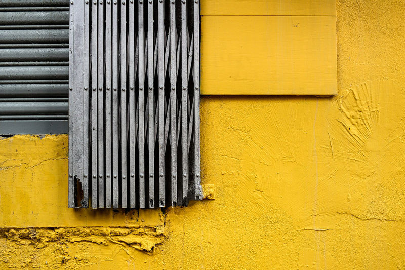 Close-up of security metal door against yellow wall
