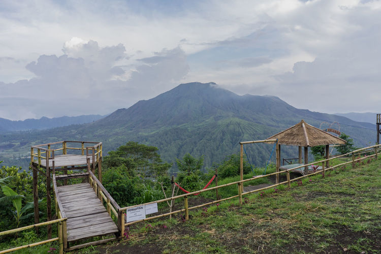 View of Mount Agung from Pinggan village, Kintamani, Bangli, Bali, Indonesia. Mountain Sky Cloud - Sky Scenics - Nature Beauty In Nature Railing Mountain Range Tranquil Scene Nature Landscape Tranquility Architecture Non-urban Scene Environment Day Built Structure No People Idyllic Land Outdoors