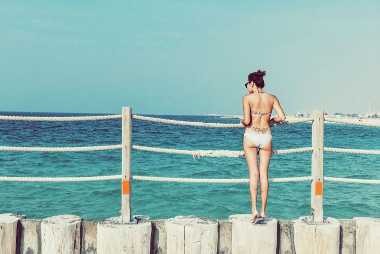 Full Length Rear View Of Young Woman Standing At A Railing