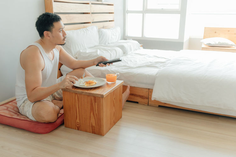 Side view of man preparing food on bed at home