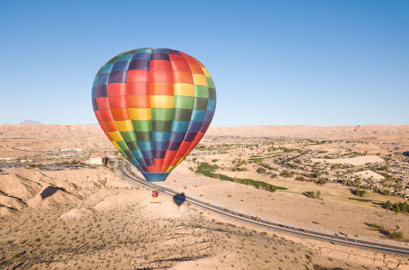 Hot air balloons in desert against clear blue sky